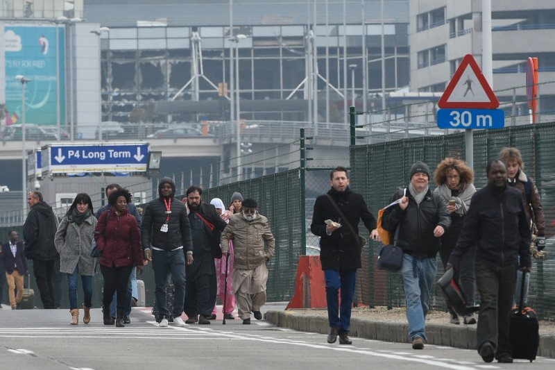 Passengers leave Brussels airport, on March 22, 2016 in Zaventem , following its evacuation after at least 13 people were killed and 35 injured as twin blasts rocked the main terminal of Brussels airport.AFP PHOTO / JOHN THYS / AFP / JOHN THYS        (Photo credit should read JOHN THYS/AFP/Getty Images)