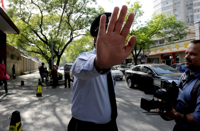 A Chinese police stops foreign journalists at a gate of the Chaoyang hospital in Beijing, where blind activist Chen Guangcheng is believed to be getting a check up, in Beijing on May 2, 2012. Chinese activist Chen Guangcheng has left the US embassy to seek medical care and join his family, officials said Wednesday, as Beijing demanded a US apology on the eve of key talks between the two powers. AFP PHOTO/Mark RALSTON        (Photo credit should read MARK RALSTON/AFP/GettyImages)