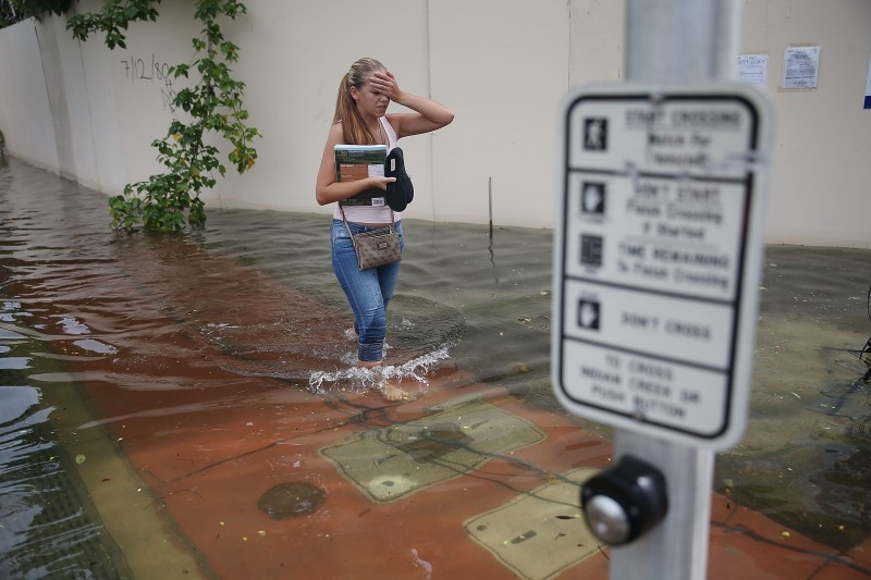MIAMI BEACH, FL - SEPTEMBER 29: Yana Kibyakova walks through a flooded street that was caused by the combination of the lunar orbit which caused seasonal high tides and what many believe is the rising sea levels due to climate change on September 29, 2015 in Miami Beach, Florida. The City of Miami Beach is in the middle of a five-year, $400 million storm water pump program and other projects that city officials hope will keep the ocean waters from inundating the city as the oceans rise even more in the future.  (Photo by Joe Raedle/Getty Images)