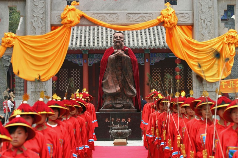 """CHANGCHUN, CHINA - SEPTEMBER 25: (CHINA OUT) Students dressed in ancient clothes stand in front of the statue of Confucius (551-479 BC), during a ceremony to worship the Chinese philosopher and educator at the Changchun Confucian Temple on September 25, 2005 in Changchun of Jilin Province, China. Various of ceremonies and celebrations are being held in China to mark the upcoming 2,556th anniversary of Confucius's birthday on September 28. During the day, the """"2005 Global Joint Confucius Memorial Ceremony"""" will be held in different Confucian Temples around China and the world. (Photo by China Photos/Getty Images)"""