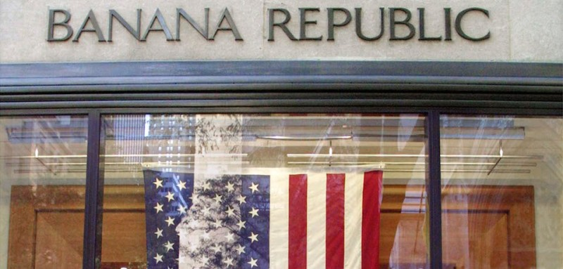 395293 02: A man walks past a large American flag hanging in the window of a Banana Republic store October 3, 2001 in New York City. The American flag has rapidly appeared in storefronts nationwide following the September 11, 2001 terrorist attacks. (Photo by Mario Tama/Getty Images)