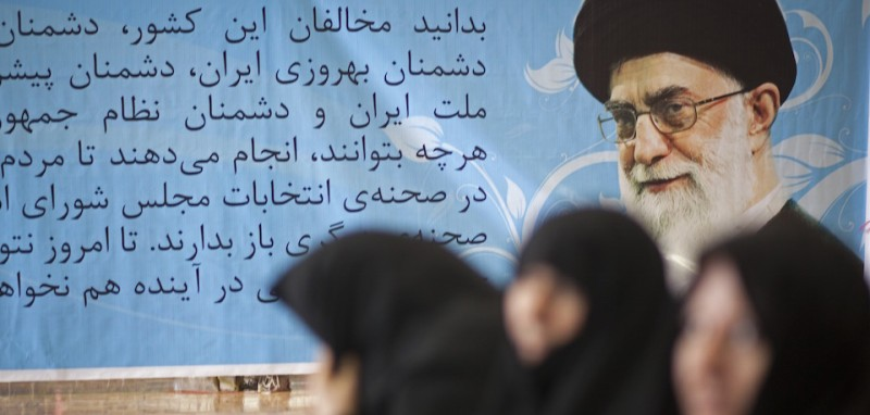 TEHRAN, IRAN - FEBRUARY 28: A posture featuring the picture of Iran's Supreme Leader Ayatollah Khamenei is passed by Iranian women outside Ali Zakani's main campaign headquarters on February 28, 2012 inTehran, Iran. Campaigning began in Iran on February 23 for the parliamentary elections due to take place on March 2, the first national poll since 2009, when the voters will chose lawmakers (known as the Majlis) for the 290 seats in the parliament.  (Photo by )