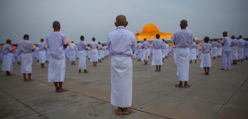 WAT DHAMMAKAYA, BANGKOK, THAILAND - 2011/03/29: The faithful gather during a mass Buddhist ordination ceremony.  More than 20,000 Buddhist novice monks gathered to offer prayers for world peace.  In Thailand men are expected to become a Buddhist monk at least once in their life. (Photo by )
