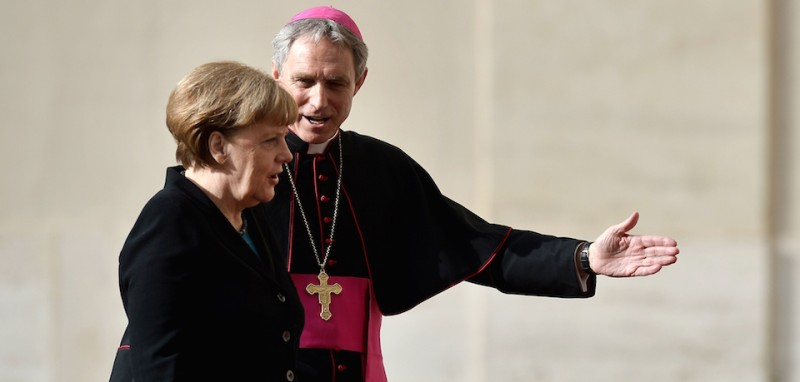 German Chancellor Angela Merkel (L) is welcome by Archbishop Georg Ganswein upon her arrival at the Vatican for a private audience with the Pope on February 21, 2015. AFP PHOTO / TIZIANA FABI        (Photo credit should read )