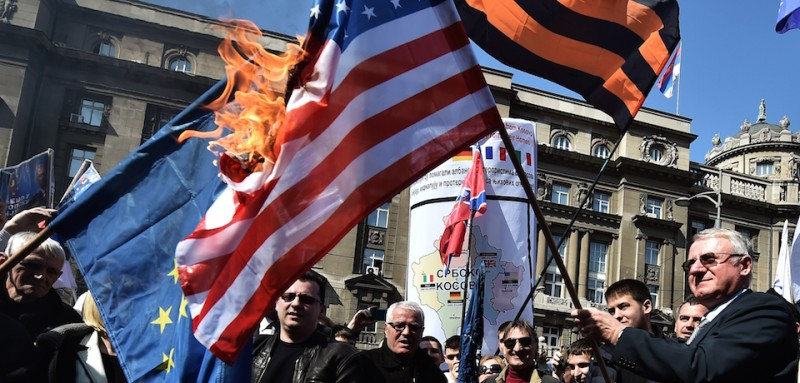 Serbian nationalist politician Vojislav Seselj (R) surrounded by his supporters holds a burning NATO flag during an anti-government rally on March 24, 2015, in front of the building of the former federal Interior Ministry in Belgrade, which was destroyed during the 1999 NATO air campaign against Serbia and Montenegro. AFP PHOTO / ANDREJ ISAKOVIC        (Photo credit should read )