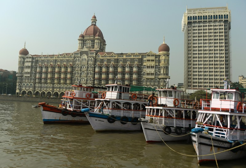 Tourist boats lie anchored near the Taj Mahal Palace hotel, one of the 2008 militant attack sites, in Mumbai on November 26, 2015. A total of 166 people were killed and more than 300 others were injured when 10 heavily-armed Islamist militants stormed the city on November 26, 2008, attacking a number of sites, including the city's main railway station, two luxury hotels, a popular tourist restaurant and a Jewish centre.  AFP PHOTO/ PUNIT PARANJPE / AFP / PUNIT PARANJPE        (Photo credit should read PUNIT PARANJPE/AFP/Getty Images)