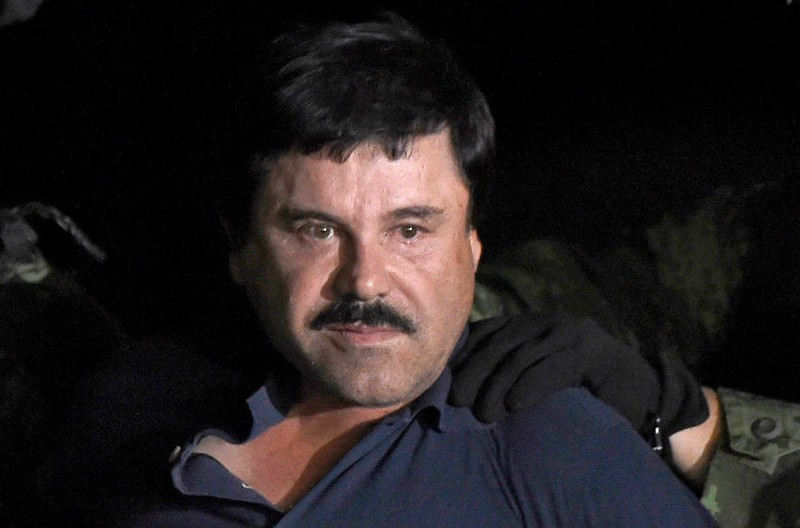 """Drug kingpin Joaquin """"El Chapo"""" Guzman is escorted into a helicopter at Mexico City's airport on January 8, 2016 following his recapture during an intense military operation in Los Mochis, in Sinaloa State. Mexican marines recaptured fugitive drug kingpin Joaquin """"El Chapo"""" Guzman on Friday in the northwest of the country, six months after his spectacular prison break embarrassed authorities.   AFP PHOTO / ALFREDO ESTRELLA / AFP / ALFREDO ESTRELLA        (Photo credit should read ALFREDO ESTRELLA/AFP/Getty Images)"""