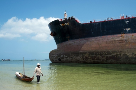 """A fisherman pulls a canoe as he walks by the Marshall Islands flagged tanker vessel """"Miracle"""" after it ran aground at the mouth of the Dar es Salaam's harbour on February 13, 2016. / AFP / DANIEL HAYDUK (Photo credit should read DANIEL HAYDUK/AFP/Getty Images)"""