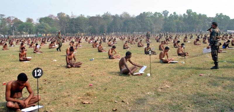 Indian army candidates sit in their underwear in a field as they take a written exam after being asked to remove their clothing to deter cheating during a recruitment day in Muzaffarpur on February 28, 2016. India's army made candidates at a recruitment day in Bihar take a written exam in their underwear to prevent them from cheating, reports said March 1, after a spate of exam cheating scandals in the eastern state. AFP PHOTO / STR / AFP / STRDEL        (Photo credit should read )