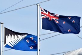 The current New Zealand flag (R) flutters next to the alternative flag (L) in Wellington on March 4, 2016.  New Zealanders began voting on March 3, on whether to adopt a new flag, in a referendum Prime Minister John Key has called a once-in-a-generation chance to ditch Britain's Union Jack from the national banner.   AFP PHOTO / MARTY MELVILLE / AFP / Marty Melville        (Photo credit should read MARTY MELVILLE/AFP/Getty Images)