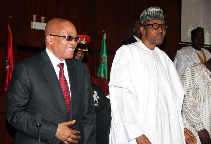 "Nigerian President Muhammadu Buhari (R) and South African President Jacob Zuma arrive for a joint sitting of the National Assembly in Abuja on March 8, 2016. South Africa's President Jacob Zuma began a two-day state visit to Nigeria on March 8, which observers see as an attempt to mend fences between the continent's largest economic powers. Pretoria is putting a positive spin on the visit, talking up the pair's ""good bilateral political, economic and social relations"" and potential new business opportunities. / AFP / PHILIP OJISUA        (Photo credit should read PHILIP OJISUA/AFP/Getty Images)"