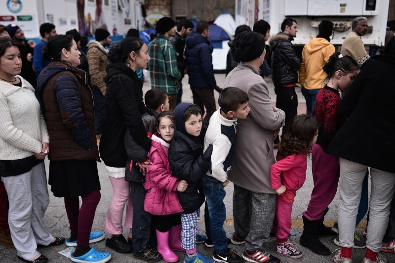 People queue for a warm meal in the port of Piraeus near Athens where thousands of stranded refugees and migrants have found a temporary shelter on March 15, 2016. The European Union said it had pushed back plans to overhaul the bloc's asylum system until next month after it has sealed a crucial migration crisis deal with Turkey. / AFP / LOUISA GOULIAMAKI        (Photo credit should read LOUISA GOULIAMAKI/AFP/Getty Images)