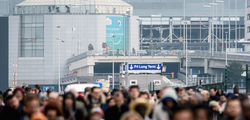 TOPSHOT - Passengers evacuate the Brussels Airport, in Zaventem, on March 22, 2016, after a string of explosions rocked Brussels airport and a city metro station, killing at least 26 people in apparently coordinated attacks, officials said.  European countries on Tuesday vowed to defend democracy against terrorism after blasts at Brussels airport and in the EU's institutional heart left at least 26 dead and dozens injured. / AFP / BELGA / DIRK WAEM / Belgium OUT        (Photo credit should read )