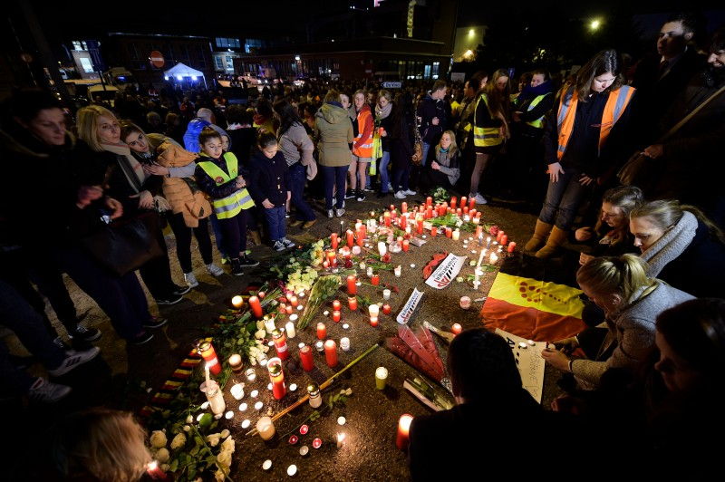 People gather around candles, floral tributes, notes and Belgian flags during a wake of Brussels Airport employees on Martch 23, 2016 in Zaventem,  a day after triple bomb attacks at the Brussels airport and at a subway train station killed 31 people and wounded more than 200. World leaders united in condemning the carnage in Brussels and vowed to combat terrorism, after Islamic State bombers attacked the symbolic heart of the EU. / AFP / BELGA AND Belga / YORICK JANSENS / Belgium OUT        (Photo credit should read YORICK JANSENS/AFP/Getty Images)