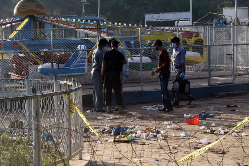 "Pakistani security officials collect evidence at the cordoned-off site of the March 27 suicide bombing, in Lahore on March 28, 2016. The toll from a suicide blast in Pakistan's Lahore rose to 69, officials said on March 28, as authorities hunted for the ""savage inhumans"" behind the attack in a park packed with Christian families celebrating Easter Sunday. More than 200 people were injured, many of them children, when explosives packed with ball bearings ripped through crowds near a children's play area in the park in Lahore, leaving dozens dead or bloodied. / AFP / ARIF ALI        (Photo credit should read ARIF ALI/AFP/Getty Images)"