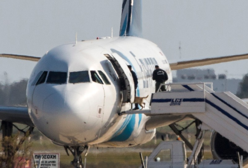 Cypriot security forces take a sniffer dog into an EgyptAir Airbus A-320 parked at the tarmac of Larnaca airport after the six-hour hijacking of the plane came to an end on March 29, 2016. Searches by Cyprus police found no explosives on the hijacker of an EgyptAir plane diverted to the island or inside the aircraft, a police source told AFP. The hijacker, who is in custody after surrendering to police following a six-hour standoff at Larnaca airport, had claimed to be wearing an explosives belt, Egyptian officials said.   / AFP / BEHROUZ MEHRI        (Photo credit should read BEHROUZ MEHRI/AFP/Getty Images)