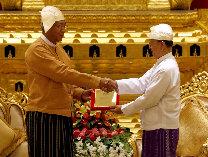 Myanmar's outgoing president Thein Sein (R) hands over the presidential seal to the country's new President Htin Kyaw (L) during the handover ceremony at the president house in Naypyidaw on March 30, 2016.  A close aide to Aung San Suu Kyi was sworn in as Myanmar's president on March 30, a role that will see him act as a proxy for the pro-democracy figurehead and carry the hopes of a nation emerging from military rule. / AFP / POOL / NYEIN CHAN NAING/POOL        (Photo credit should read NYEIN CHAN NAING/POOL/AFP/Getty Images)