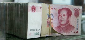 """CHENGDU, CHINA - MAY 26: (CHINA OUT; PHOTOCOME OUT) A bank teller puts Chinese currency 100 yuan (or Renminbi) notes on the counter on May 26, 2005 in Chengdu of Sichuan Province, China. China is under fierce pressure to free up the yuan, particularly from the United States. China's central bank, the People's Bank of China said in its first quarter report that China will keep its currency stable at a """"reasonable and well-balanced level"""" while improving the yuan's exchange rate mechanism.(Photo by China Photos/Getty Images)"""
