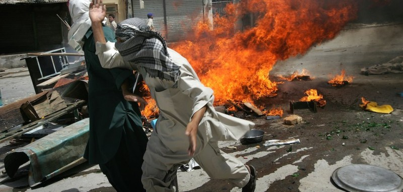 QUETTA, PAKISTAN - AUGUST 29:  Rioters run past burning debris during a violent demonstration August 29, 2006 in Quetta, Pakistan. More than a thousand angry Baloch took to the streets following a prayer service for slain tribal leader Nawab Bugti, who died in a clash with Pakistani army troops over the weekend. The mob torched buildings and cars and looted stores before police scattered them with tear gas and warning shots.  (Photo by John Moore/Getty Images)