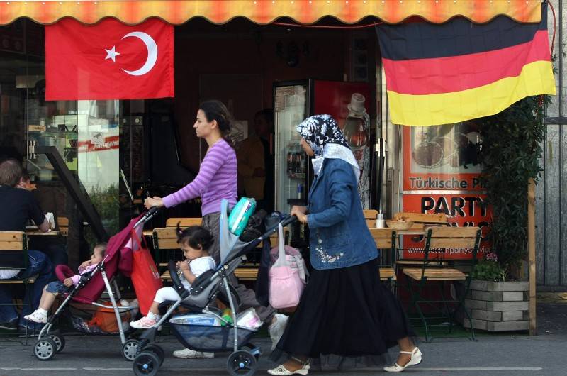 BERLIN - JUNE 23:  A Muslim woman wearing a headscarf pushes a pram past German and Turkish flags fluttering from the awning of a cafe in the immigrant-heavy district of Wedding two days ahead of the Germany vs. Turkey Euro 2008 semi-finals football match on June 23, 2008 in Berlin, Germany. Germany is home to more Turks than any other country outside Turkey, and many analysts predict fan reaction to the game will be characterized by inter-ethnic unity rather than confrontation.  (Photo by Sean Gallup/Getty Images)