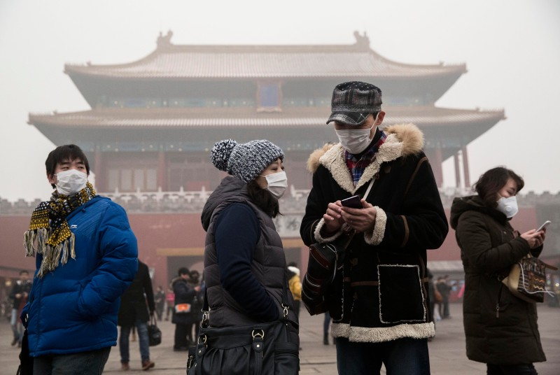 BEIJING, CHINA - DECEMBER 01: Chinese tourists wear masks as protection from the pollution outside the Forbidden City during a day of high pollution on December 1, 2015 in Beijing, China. China's capital and many cities in the northern part of the country recorded the worst smog of the year with air quality devices in some areas unable to read such high levels of pollutants. Levels of PM 2.5, considered the most hazardous, crossed 600 units in Beijing, nearly 25 times the acceptable standard set by the World Health Organization. The governments of more than 190 countries are meeting in Paris this week to set targets on reducing carbon emissions in an attempt to forge a new global agreement on climate change. (Photo by Kevin Frayer/Getty Images)