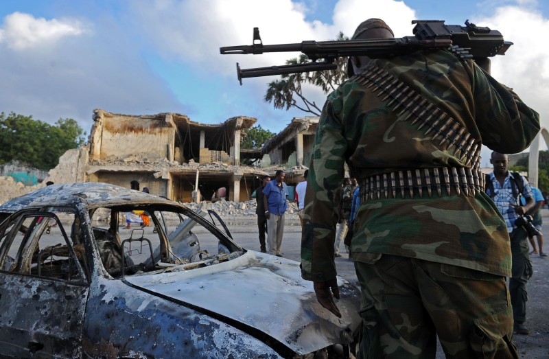 Somali soldiers and resident stand near wreckage car and buildings on February 27, 2016, in Mogadishu, Somalia. At least 14 people were killed on February 26 as twin blasts and gunfire rocked a hotel and neighbouring park in central Mogadishu, police said, in an attack claimed by the Al-Qaeda-linked Shebab militants. / AFP / MOHAMED ABDIWAHAB        (Photo credit should read MOHAMED ABDIWAHAB/AFP/Getty Images)