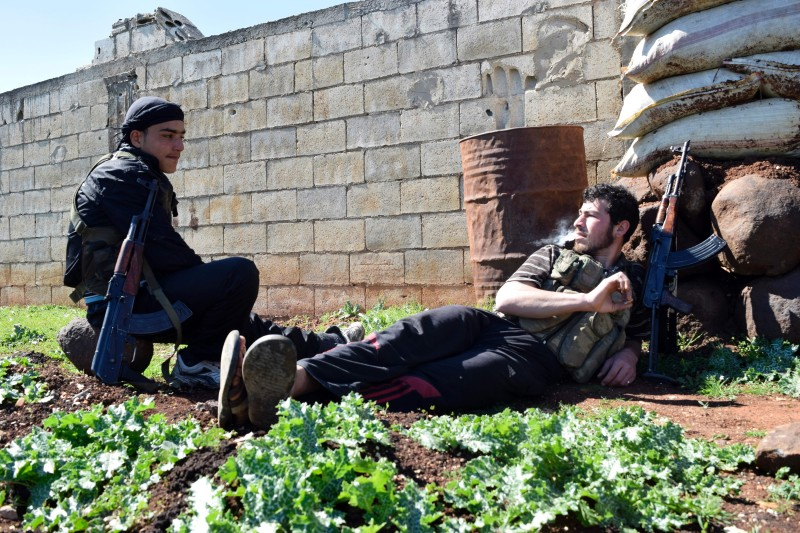 Syrian rebel fighters rest in a field as they hold a position near the frontline on March 1, 2016 in the countryside on the outskirts of the central Syrian city of Homs, as Syria truce enters day four.   The ceasefire applies to Damascus and most of its suburbs, the southern province of Daraa, and parts of Aleppo and Homs provinces but does not apply to territory held by the Islamic State group and Al-Qaeda affiliate Al-Nusra Front.     / AFP / MAHMOUD TAHA        (Photo credit should read MAHMOUD TAHA/AFP/Getty Images)