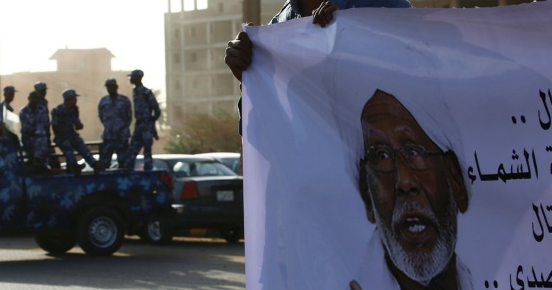 A mourner holds a banner bearing a portrait of Veteran Sudan Islamist opposition leader Hassan al-Turabi during his funeral on March 6, 2016 in the capital Khartoum. Turabi, one of the fiercest critics of President Omar al-Bashir's government, died of a heart attack on March 5 aged 84, officials said. / AFP / ASHRAF SHAZLY        (Photo credit should read ASHRAF SHAZLY/AFP/Getty Images)