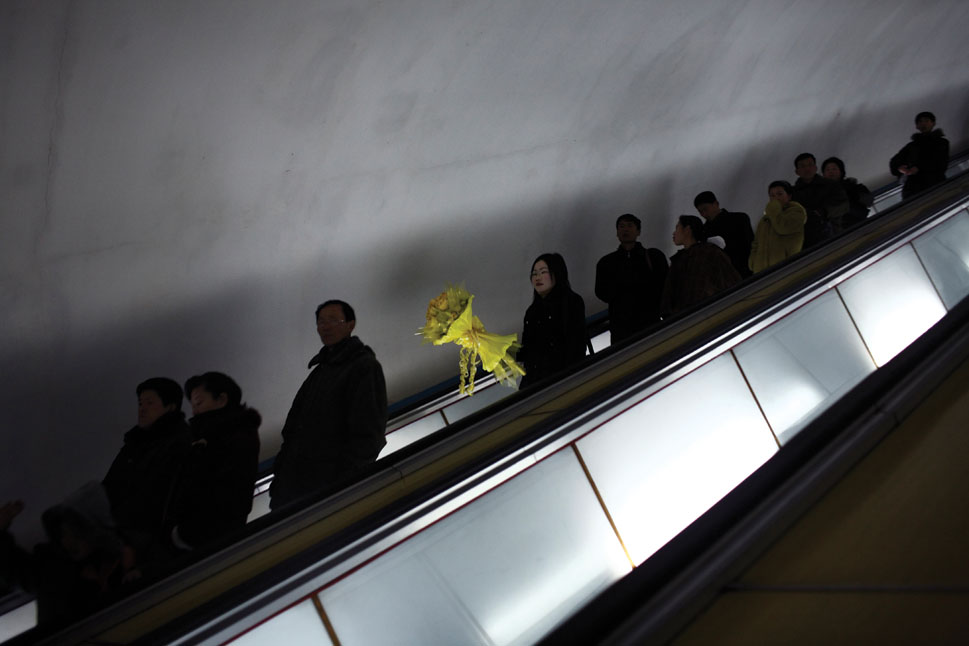 A woman carries a bouquet of yellow flowers down the escalator into a Pyongyang metro subway.