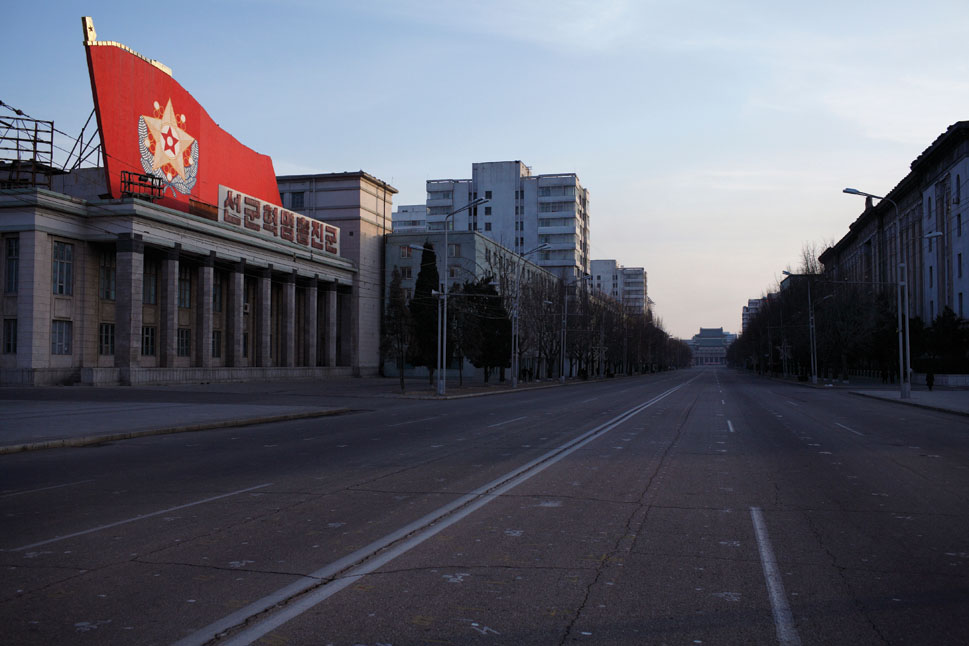 A six-lane boulevard empty of traffic passes through Kim Il Sung Square, the main square of Pyongyang.