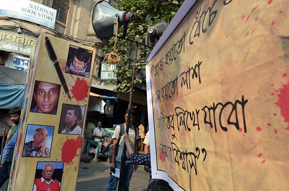 A Indian student looks from behind a poster with pictures of recently killed Bangladeshi bloggers during a protest meeting organised to pay homage in Kolkata on May 16, 2015.  The recent series of attacks on bloggers in Bangladesh, with the latest victim Ananta Bijoy Das mowed down by killers, is claimed to be Islamic fundamentalists affiliated to various militant groups. These groups have targeted bloggers for their secular views on the internet over the last few years.   AFP PHOTO/ Dibyangshu Sarkar        (Photo credit should read DIBYANGSHU SARKAR/AFP/Getty Images)