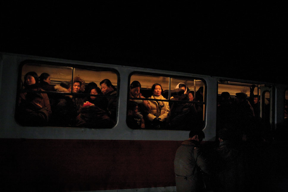 People fill a tram streetcar at night in Pyongyang.