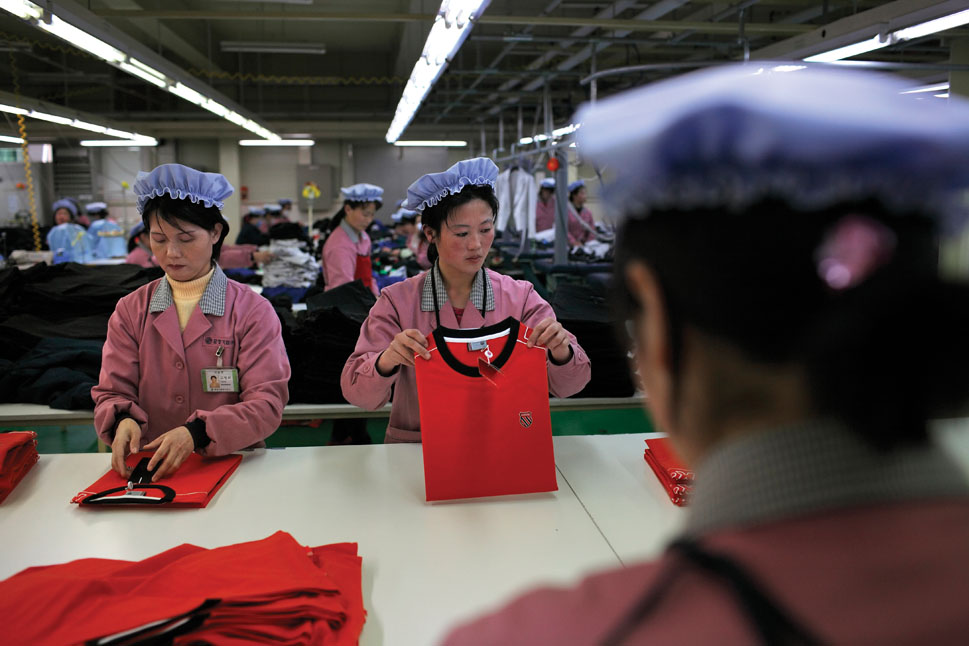 Women fold shirts marked with the logo of the American clothing company K-SWISS at a factory inside the Kaesong Industrial Region. The special industrial park is run by a South Korean committee and developed by the South Korean conglomerate Hyundai which offers leases to other South Korean companies. The companies employ North Korean workers with wages starting as low as 30 USD per month, the lowest in Asia.