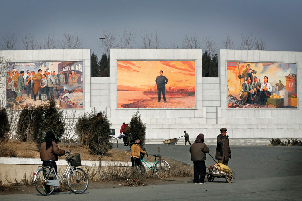 People walk past massive propaganda mosaics of Kim Jong Il and Kim Il Sung on the outskirts of Pyongyang.