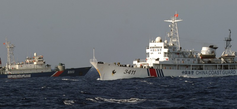 This picture taken from a Vietnam Coast Guard ship on May 14, 2014 shows a Vietnamese Coast Guard ship (L) is challended by a  China Coast Guard ship  near to the site of a Chinese drilling oil rig (R, background) being installed at the disputed water in the South China Sea off Vietnam's central coast. Vietnam National Assembly's deputies gathered for their summer session are discussing the escalating tension with China over the South China Sea's contested water. AFP PHOTO/HOANG DINH Nam        (Photo credit should read HOANG DINH NAM/AFP/Getty Images)