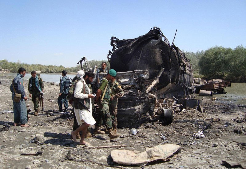 Members of the security forces walk at the site of a NATO airstrike which destroyed two fuel tankers hijacked by the Taliban in northern Kunduz on September 4, 2009.  A NATO airstrike destroyed two fuel tankers hijacked by the Taliban in Afghanistan, igniting a fireball that an Afghan official said killed about 90 people - mostly insurgents.  AFP PHOTO/STR (Photo credit should read STR/AFP/Getty Images)