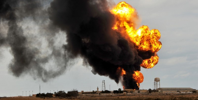Flames and heavy black smoke rise from an oil pipe that was hit in a blast near an oil facility in the town of Ras Lanuf on March 9, 2011.  AFP PHOTO/ROBERTO SCHMIDT (Photo credit should read ROBERTO SCHMIDT/AFP/Getty Images)