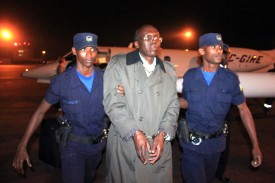 Rwandan fugitive Leon Mugesera (C) is escorted handcuffed by policemen to a police vehicle on the tarmac as he arrives at Kigali International Airport late on January 24, 2012. Mugesera, a linguist who had lived in Canada since 1993, is wanted by the Rwandan authorities for alleged incitement to genocide in a speech he delivered two years before the 1994 genocide that claimed the lives of 800,000 people, mainly minority Tutsis. (Photo credit should read STEVE TERRILL/AFP/Getty Images)