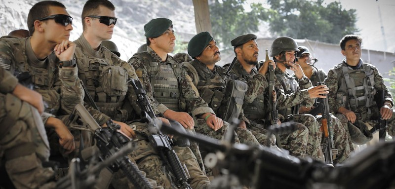 US and Afghan soldiers listen to a mission briefing before a combined patrol southwards towards the village of Kandagal in the Pech valley, 16th June 2012