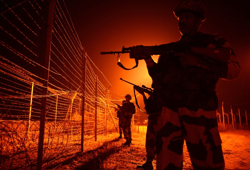 Indian Border Security Force (BSF) soldiers patrol along the border fence at an outpost along the India-Pakistan border in Abdulian, 38 kms southwest of Jammu, on January 17, 2013.  A ceasefire took hold January 17 in disputed Kashmir after the Indian and Pakistani armies agreed to halt deadly cross-border firing that had threatened to unravel a fragile peace process. AFP PHOTO/Tauseef MUSTAFA        (Photo credit should read TAUSEEF MUSTAFA/AFP/Getty Images)