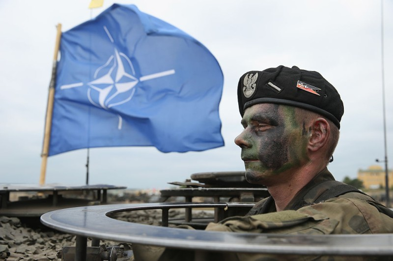 ZAGAN, POLAND - JUNE 18:  A soldier of the Polish Army mans a tank as a NATO flag flies behind during the NATO Noble Jump military exercises of the VJTF forces on June 18, 2015 in Zagan, Poland. The VJTF, the Very High Readiness Joint Task Force, is NATO's response to Russia's annexation of Crimea and the conflict in eastern Ukraine. Troops from Germany, Norway, Belgium, Poland, Czech Republic, Lithuania and Holland were among those taking part today.  (Photo by Sean Gallup/Getty Images)