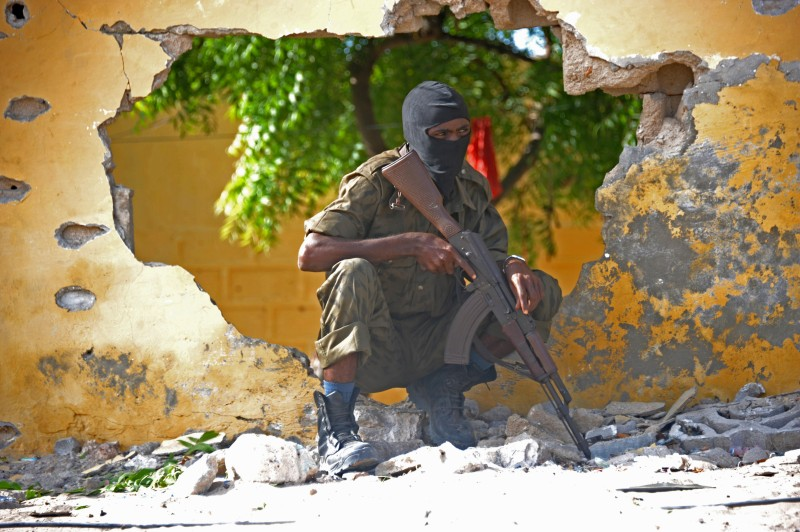 A Somali soldier stands guard next to the site where Al Shebab militants carried out a suicide attack against a military intelligence base in Mogadishu on June 21, 2015. Shebab militants launched a major suicide raid on June 21 against a military intelligence base in the capital Mogadishu, setting off a car bomb before storming inside, security officials said. Somalia's interior ministry said the three attackers were all killed in the raid, and that Somali security forces who fought them suffered no casualties. AFP PHOTO / MOHAMED ABDIWAHAB        (Photo credit should read Mohamed Abdiwahab/AFP/Getty Images)