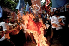 Turkish nationalists burn a Chinese flag, during a protest to denounce China's treatment of ethnic Uighur Muslims, in front of the Chinese consulate in Istanbul, on July 5, 2015. Turkish media reported restrictions on Muslim Uighurs worshipping and fasting during the holy month of Ramadan. Beijing in turn denied the allegations and demanded that Turkey clarify its statements.  AFP PHOTO / OZAN KOSE        (Photo credit should read OZAN KOSE/AFP/Getty Images)