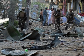 Afghan security forces and residents  inspect the site of a powerful truck bomb explosion in Kabul on August 7, 2015. A powerful truck bomb killed at least seven people and wounded more than 100 others, officials said, the first major attack in the Afghan capital since the announcement of Taliban leader Mullah Omar's death. AFP PHOTO / Wakil Kohsar        (Photo credit should read WAKIL KOHSAR/AFP/Getty Images)