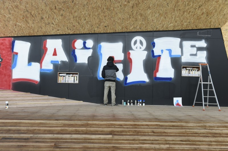 "TOPSHOT - A street artist writes ""Laicite"" during the inauguration of ""Place de La Laicite"" (Secularism Square) in Paris on December 9, 2015. / AFP / ALAIN JOCARD / RESTRICTED TO EDITORIAL USE - MANDATORY MENTION OF THE ARTIST UPON PUBLICATION - TO ILLUSTRATE THE EVENT AS SPECIFIED IN THE CAPTION        (Photo credit should read ALAIN JOCARD/AFP/Getty Images)"