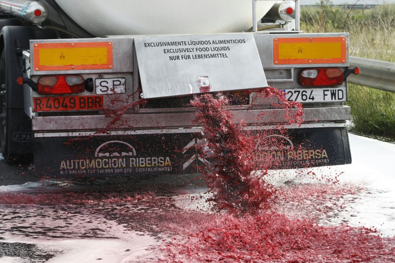 Wine flows from the tap of a Spanish truck's tanker on April 4, 2016 in Le Boulon, ten kilometers from the French-Spanish border, during a demonstration of French winemakers against southern countries' wine imports.   The demonstrators, claiming that the cheap wine from Spain and Italy represent an unfair competition for French wines, stopped the Spanish trucks carrying wine, and partially or totally emptied their tankers. / AFP / RAYMOND ROIG        (Photo credit should read RAYMOND ROIG/AFP/Getty Images)