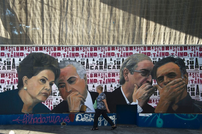 A woman walks past a mural depicting the president of the Brazilian lower house of Congress Eduardo Cunha (2-R) speaking with the president of the Brazilian Social Democracy Party (PSDB) Aecio Neves (R) as if they were conspiring against Brazilian President Dilma Rousseff (L), who is depicted speaking with Vice-President Michel Temer, at Paulista Avenue in Sao Paulo, Brazil on April 19, 2016. Brazil woke Monday to deep political crisis after lawmakers authorized impeachment proceedings against President Dilma Rousseff, sparking claims that democracy was under threat in Latin America's biggest country. / AFP / NELSON ALMEIDA        (Photo credit should read NELSON ALMEIDA/AFP/Getty Images)
