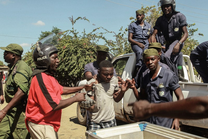 Zambian Police apprehend an alleged looter in the Zingalume Compound where residents have attacked broken and looted foreign-run shops in Lusaka on April 19, 2016.  Zambian authorities arrested more than 200 people for rioting and ransacking Rwandan-owned shops in Lusaka over allegations that foreigners were behind a string of ritual killings, a minister said.  / AFP / SALIM DAWOOD        (Photo credit should read SALIM DAWOOD/AFP/Getty Images)