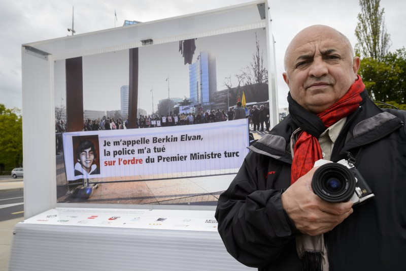 "Swiss photojournalist Demir Sonmez poses on April 25, 2016 next to a picture showing a demonstation he took at the Place des Nations in Geneva.  Turkey has asked Geneva authorities to remove a picture used by demonstrators that blames President Recep Tayyip Erdogan for the killing of teenage opposition symbol Berkin Elvan, a Swiss official said on April 25, 2016. The picture is part of an exhibition outside the United Nations complex in Geneva, supported by the city of Geneva and campaign group Reporters Without Borders. The photographer Demir Sonmez, a Swiss citizen of Kurdish and Armenian origin who told AFP his objective was to highlight ""the multiple struggles of the people.""  / AFP / FABRICE COFFRINI        (Photo credit should read FABRICE COFFRINI/AFP/Getty Images)"