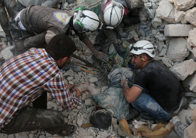Syrian civil defence volunteers remove the body of a man from the rubble of destroyed buildings following reported airstrikes on April 27, 2016 in the rebel-held eastern neighbourhood of Bab al-Nayrab in the city of Aleppo. Air strikes and clashes in Syria's second city Aleppo killed at least 12 people, state media and emergency workers said, part of a surge in violence straining a two-month-old ceasefire. State news agency SANA said that seven people were killed and 35 wounded by rocket and gunfire in several neighbourhoods that it blamed on Al-Qaeda affiliate Al-Nusra Front and its allies. In rebel-held eastern Aleppo, five civilians were killed in two neighbourhoods, according to the civil defence, known as White Helmets. An AFP correspondent said that regime aircraft targeted one area with barrel bombs and another with missiles. / AFP / AMEER ALHALBI        (Photo credit should read AMEER ALHALBI/AFP/Getty Images)